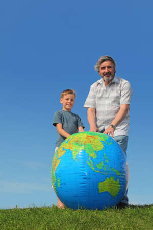 boy and his grandfather standing on lawn near big inflatable globe and smiling Stock Photo - 17724310