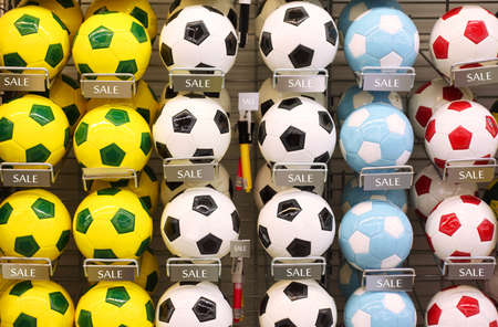 shoppings: Rows of white, yellow and blue classic soccer balls in store Stock Photo