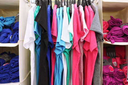 Variety of multicolored casual clothes in shop; T-shirts hang on racks and rolled into rolls Stock Photo - 17676827