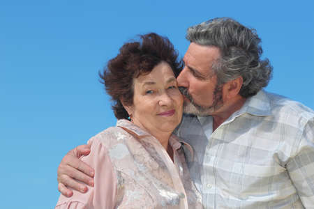 portrait of old man embracing woman and kissing her cheek, blue sky Stock Photo - 17724623