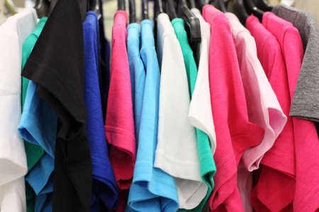 Variety of multicolored casual clothes in shop; T-shirts hanging on hangers