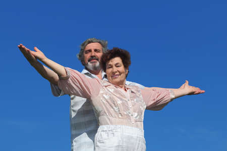 happy old man: old man and woman standing, smiling and looking at camera, hands apart, blue sky