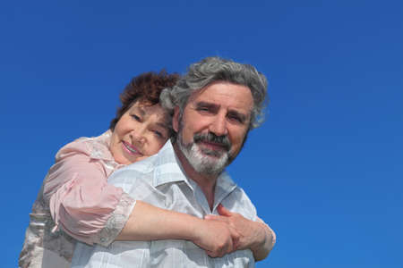 old woman embracing man from back and smiling, blue sky Stock Photo - 17724472