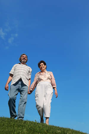 old man and woman standing on hill and holding for hands, blue sky and green lawn Stock Photo - 17724477