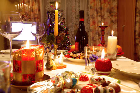 Decorated christmas dining table with glasses and christmas tree in background  photo