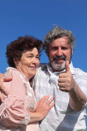 old man and woman embracing, man making thumbs up gesture, blue sky Stock Photo - 17724621