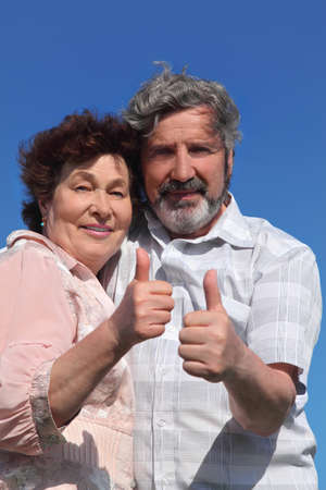 old man and woman making thumbs up gesture, blue sky Stock Photo - 17724624