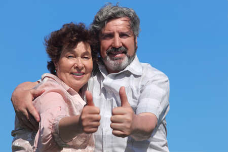 old man and woman making thumbs up gesture and smiling, blue sky Stock Photo - 17724493
