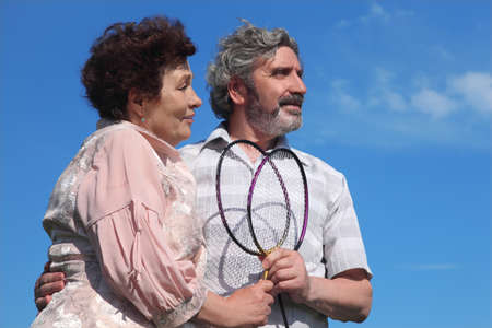 old man and woman embracing, holding badminton rackets, blue sky Stock Photo - 17724618