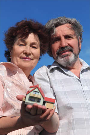 little model: old man and woman holding little model of house, blue sky