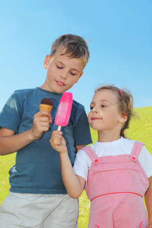 little boy and girl holding ice-creams and showing it to each other, blue sky and green lawn photo