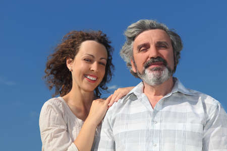 heir: portrait of young woman embracing her father and smiling, blue sky Stock Photo