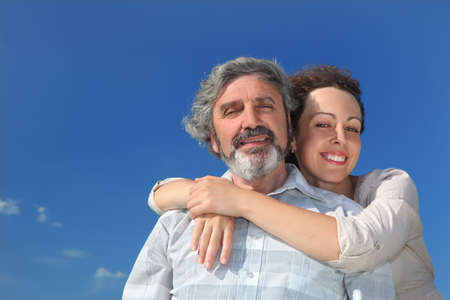 portrait of young woman embracing her father from back and smiling, blue sky