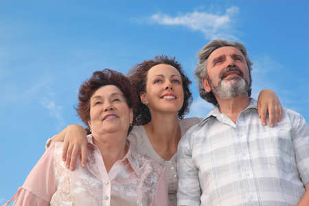 heir: family of adult woman and her parents embracing and smiling, looking up, blue sky