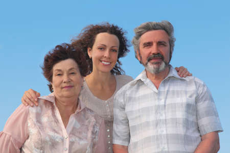 family of adult woman and her parents embracing and smiling, blue sky Stock Photo - 17724309