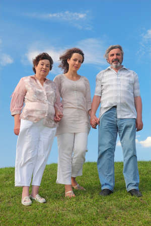 family of adult woman and her parents standing on lawn and holding for hands, blue sky Stock Photo - 17724645