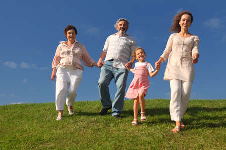 family with little girl, mother and grandparents holding for hands and walking on lawn Stock Photo - 17724487