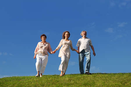 adult daughter and her parents holding for hands and walking on lawn Stock Photo - 17724470