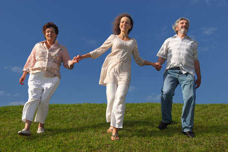 adult daughter and her parents holding for hands, smiling and walking on lawn Stock Photo - 17724637