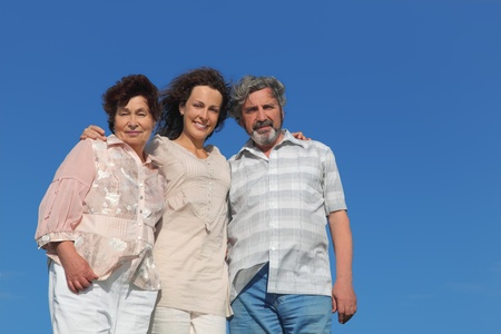 portrait of adult daughter and her parents embracing and smiling, blue sky Stock Photo - 17724473