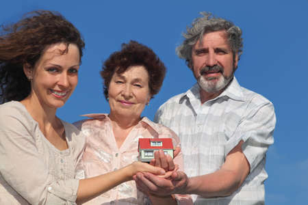 adult daughter and her parents holding house model and smiling, blue sky photo