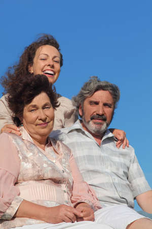 adult daughter embracing her parents and smiling, blue sky, focus on mother photo