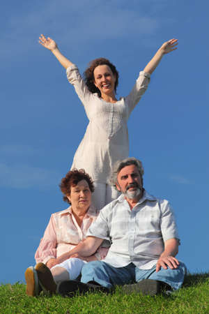 adult daughter with apart hands, her parents sitting on summer lawn photo
