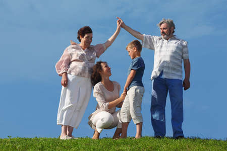 mother and son holding for hands, grandparents making house roof gesture, summer lawn photo