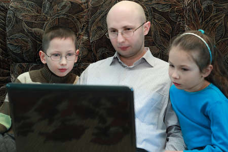 bald girl: Father, son and daughter sitting on couch and look at laptop screen, serious faces