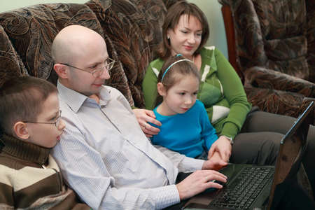 bald girl: Father, mother, son and daughter sitting on couch and look at laptop screen, focus on man
