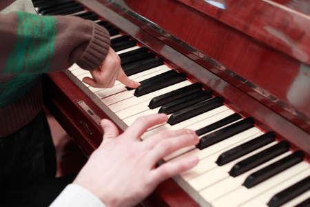 tocando piano: manos de un padre e hijo que juegan en marrón piano, teclas blancas y negras