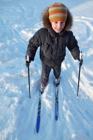 little boy in warm sport clothes skiing and smiling at winter photo
