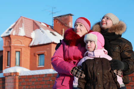 father, mother and daughter standing outdoors in winter near house and looking in sky, focus on girl  Stock Photo - 17724495