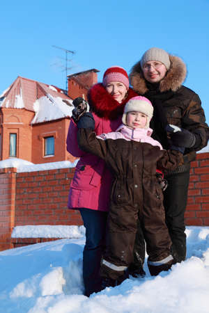 father, mother and daughter standing outdoors in winter near house, father and mother holding daughters hands photo