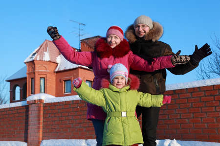 father, mother and daughter standing and spread arms outdoors in winter near house Stock Photo - 17724494