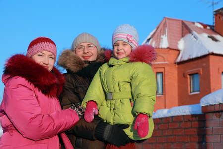 father, mother and daughter standing outdoors in winter near house, father and father holding daughter in hands Stock Photo - 17724511