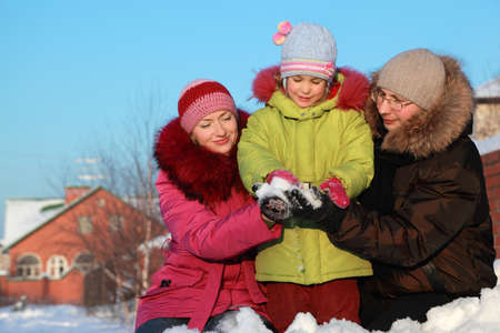father and mother offer to daughter to make snowball outdoors in winter near house, father and mother sitting Stock Photo - 17724564