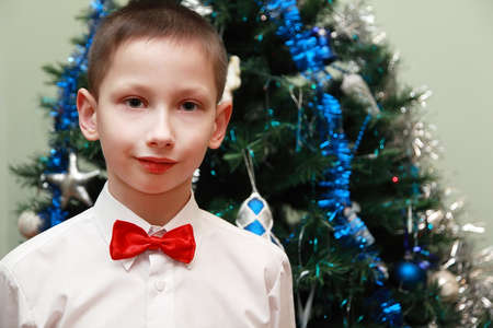 nouse: boy in white shirt and red bow tie standing near Christmas tree