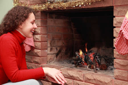 gaud: beautiful young woman in red sweater sits near fireplace and smiles