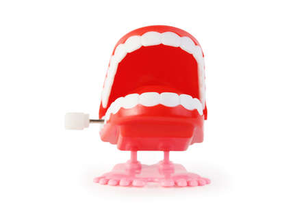 ivories: front view of toy clockwork open jaw with white teeth on pink legs on white background Stock Photo