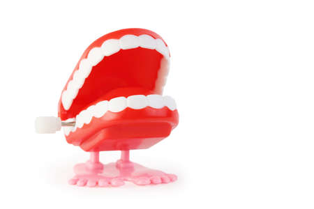 ivories: toy clockwork open jaw with white teeth on pink legs on white background