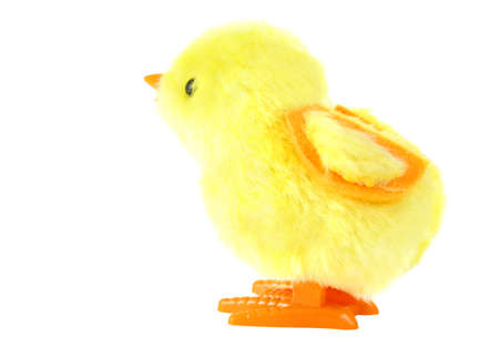 diurnal: side view of clockwork toy fluffy yellow chick with orange feet isolated on white background Stock Photo