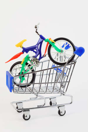 colorful plastic toy two-wheeled bicycle in purchasing cart on white background Stock Photo - 17674730