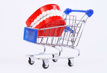 ivories: small toy jaw with white teeth in purchasing cart on white background