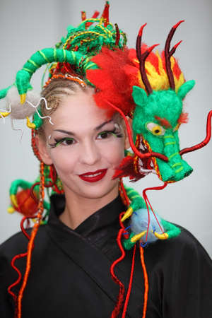 braiding: MOSCOW - OCTOBER 2: Smiling model with fanciful braiding hairdo Chinese Dragon&quot, at XVII International Festival World of Beauty - 2010 in exhibition complex Gostiny Dvor, on October 2, 2010 in Moscow, Russia.