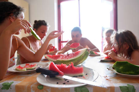 family eats juicy watermelon. Focus on plate with piece of watermelon and knife photo
