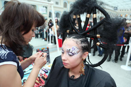 visagiste: MOSCOW - OCTOBER 2: Visagiste makes makeup for model with punk hairstyle at XVII International Festival World of Beauty - 2010 in exhibition complex Gostiny Dvor, on October 2, 2010 in Moscow, Russia. Editorial