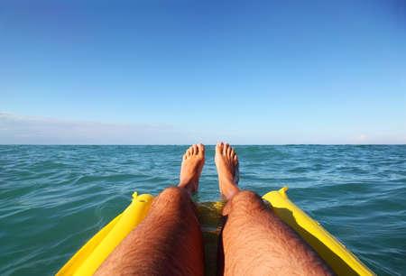 mandatoriccio: mens feet on yellow inflatable mattress, ocean, far horizon
