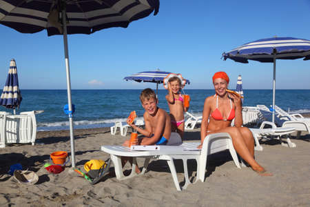 young mother, little son and daughter sitting on lounge on beach and eating pizza, focus on boy Stock Photo - 17932965