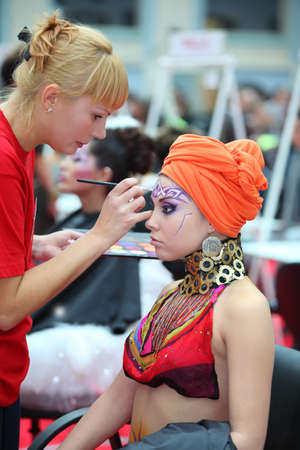 visagiste: MOSCOW - OCTOBER 2: Visagiste makes makeup for model wear arab turban at XVII International Festival World of Beauty - 2010 in exhibition complex Gostiny Dvor, on October 2, 2010 in Moscow, Russia.
